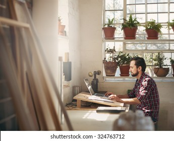 Young male designer sitting and working on his laptop in an office space in his creative design studio