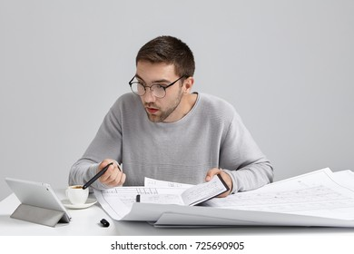 Young male designer stares in screen of tablet, has deadline to finish drawing sketches, being busy and overworked. Creative male office worker look for spare day to meet with companions or colleagues