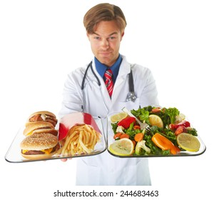 Young male doctor holding dishes of healthy and unhealthy food over white background