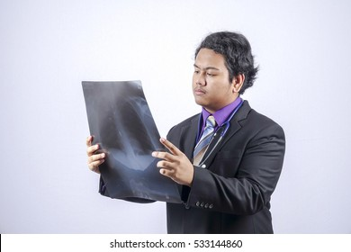 Young male doctor looking at the x-ray picture of lungs .