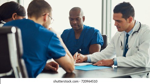 Young male doctor on medical staff meeting, showing his colleagues something in journal, making notes