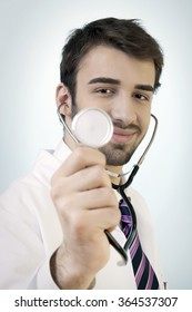 Young male doctor is posing with confidence. Standing in front of a blue background with a vignette and bright point in the middle to stand out the model.