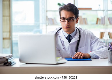 Young male doctor sitting at desk in hospital clinic