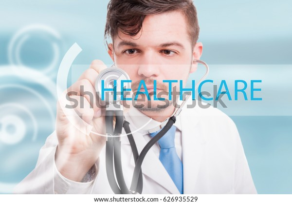 Young male doctor touching icon of media screen and listening with stethoscope