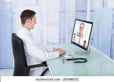 Young male doctor video conferencing with colleagues through computer in hospital