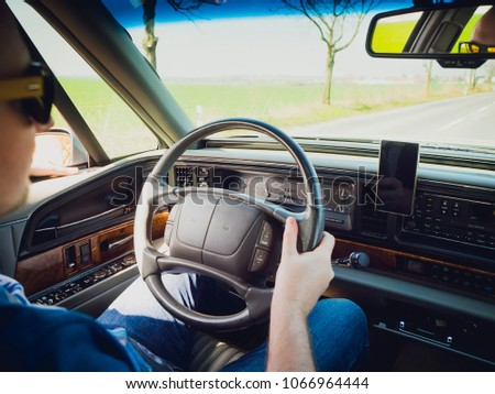 Young male driver behind the wheel of a vintage luxury car