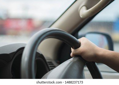 Young male driving behind the wheel.