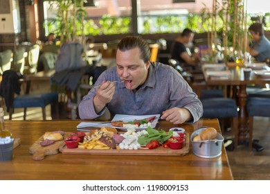 young male eats meat in the restaurant at breakfast