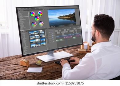 Young Male Editor Editing Video On Computer At Workplace