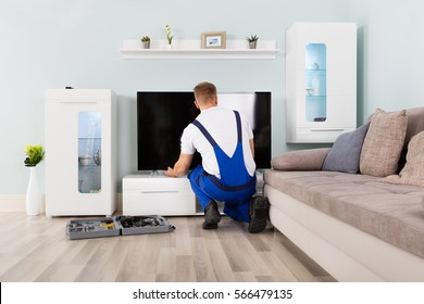 Young Male Electrician Fixing Television With Digital Multimeter