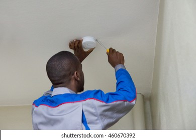 Young Male Electrician Installing Fire Sensor On A Ceiling