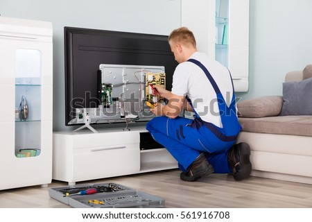 Young Male Electrician In Overall Checking Television