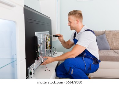 Young Male Electrician Repairing Television With Screwdriver