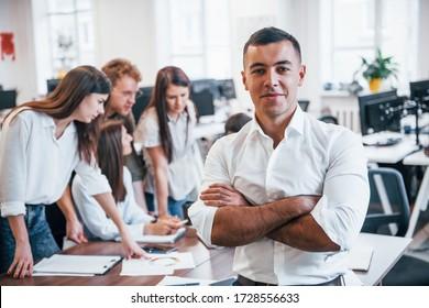 Junge männliche Angestellte in formalen Kleidungsstücken, die im Büro stehen. Gruppe von Leuten, die hinter uns arbeiten.