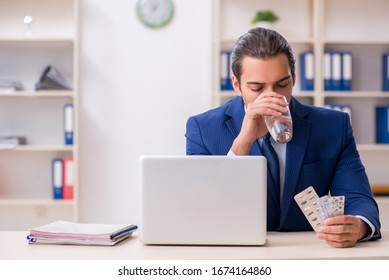 Young male employee and a lot of pills on the desk