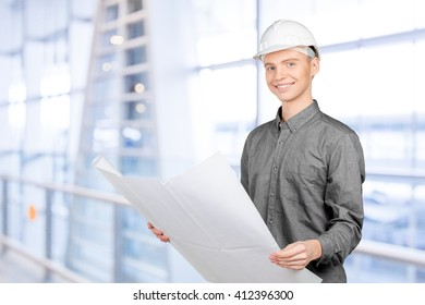 Young male engineer with helmet holding blueprint
