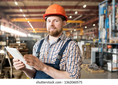 Young male engineer in helmet and overalls looking for technical data in the net while working in factory