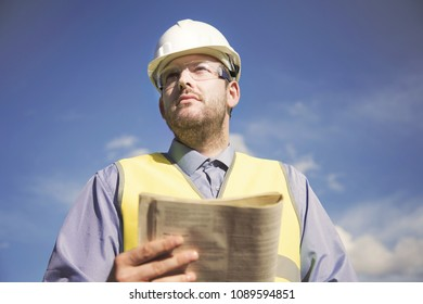 Young male engineer in a white helmet, safety glasses and a yellow vest against a blue sky