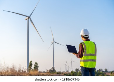 young male engineer working with laptop computer against wind turbine farm