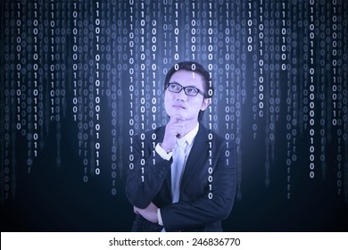 Young male entrepreneur in business suit, looking at binary code in futuristic computer screen