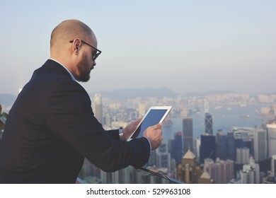 Young male entrepreneur monitoring business rate of companies successfulness via touch pad with mock up screen standing on roof of skyscraper with copy space area for your advertising message
