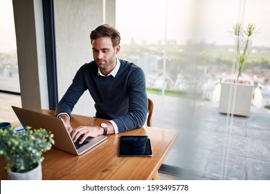 Young male entrepreneur sitting at his dining room table at home working online with a laptop