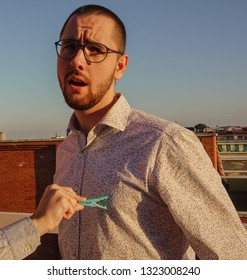 Young male expresses pain and pleasure, because a hand is closing a blue plastic clothespin on his nipple. He is wearing a colorful hipster shirt, apparently he enjoys this sadomasochism experience.