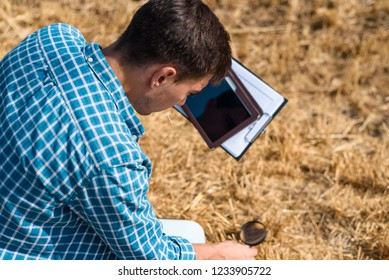 Young male farmer agronomist botanist studies mowed hay with a magnifying glass and tablet in the field view from the back
