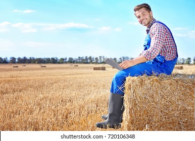 Young male farmer holding laptop in wheat field