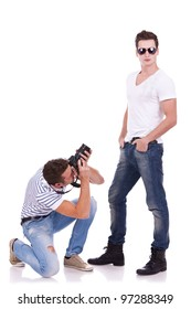 young male fashion model posing for a professional photographer on white background. young man wearing sunglasses being photographed by a young artist