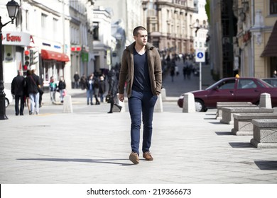 Young male fashion model walking in street