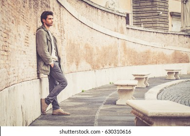 Young male fashion street on wall. A beautiful young man wearing winter clothes in the street. Pants, white sweater and green long coat. Hands in his pockets, leaning on an old wall.