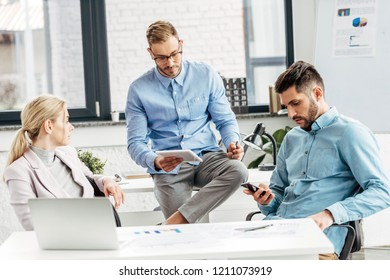 young male and female business colleagues working together in office