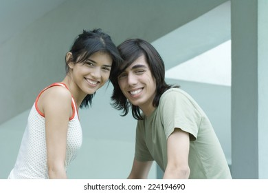 Young male and female friends, waist up, looking at camera