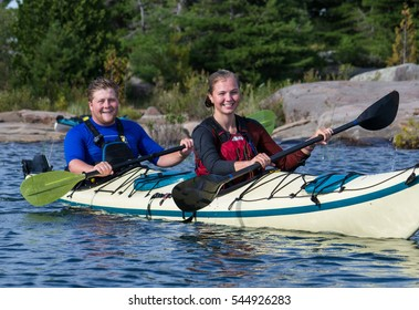 Young male and female kayaking in a tandem kayak in a lake