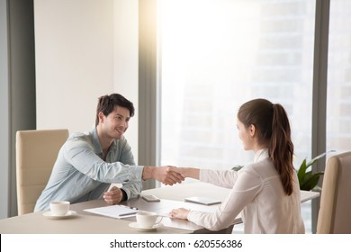 Young male and female partners handshaking over the office table, showing mutual respect, greeting and starting negotiations, closing a deal or making an agreement sitting by the window