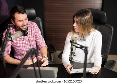 Young male and female radio hosts talking with each other during a live radio show