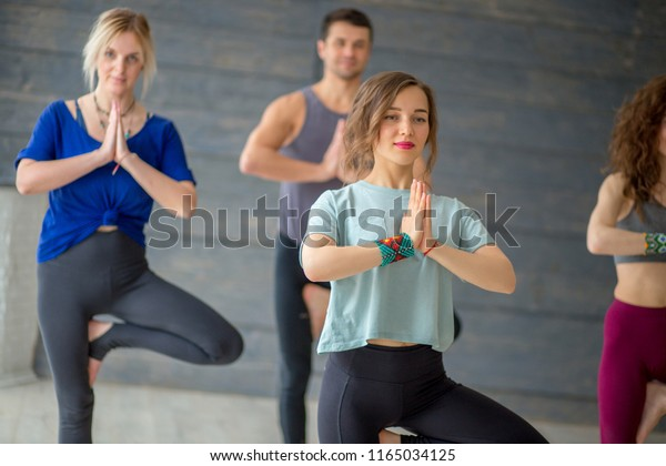 Young male and female students doing yoga exercise in college sport hall standing in Tree Pose, Vrksasana Posture, taking off tension of exams time