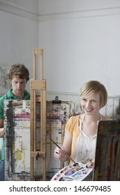 Young male and female students painting at easels in art class
