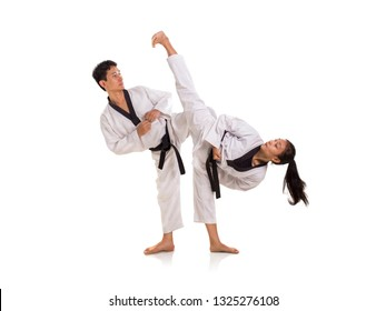 Young male and female taekwondo black belt masters in a sparring session. Full body shot on white background