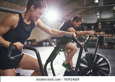 Young male and female wearing sportswear riding toughly cycling machines in light modern gym.