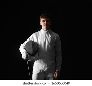 Young male fencer on dark background