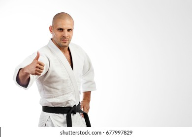 Young male fighter in a white kimono with black belt for judo, jujitsu posing on isolated white background, holding a thumb up