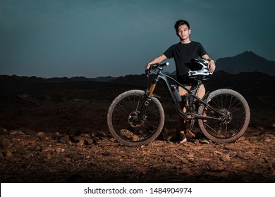 Young male Filipino teenager posing with his 29 inch full suspension mountain bike with a full faced helmet in the mountains of Ras Al Khaimah, United Arab Emirates