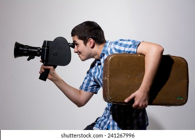Young male filmmaker with old movie camera and a suitcase in his hand. Traveler with a camera