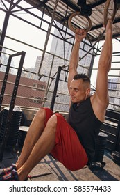 Young male fitness model training at the outdoor gym with rings