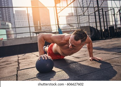 Young male fitness model training at the outdoor gym with heavy ball