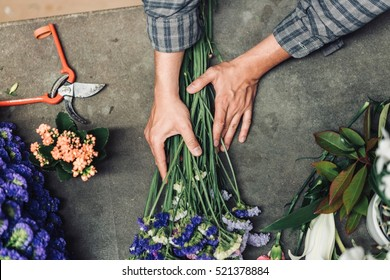 Young male florist working at counter in flower shop