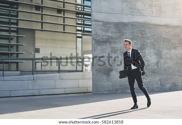 Young male in formal dark suit with skateboard at hand walking in hurry down bright street