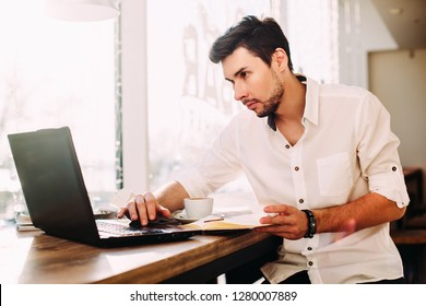 Young male freelancer chatting on mobile phone while sitting front open laptop computer in natural food cafe, handsome man reading text message during work on net-book in comfortable coffee shop